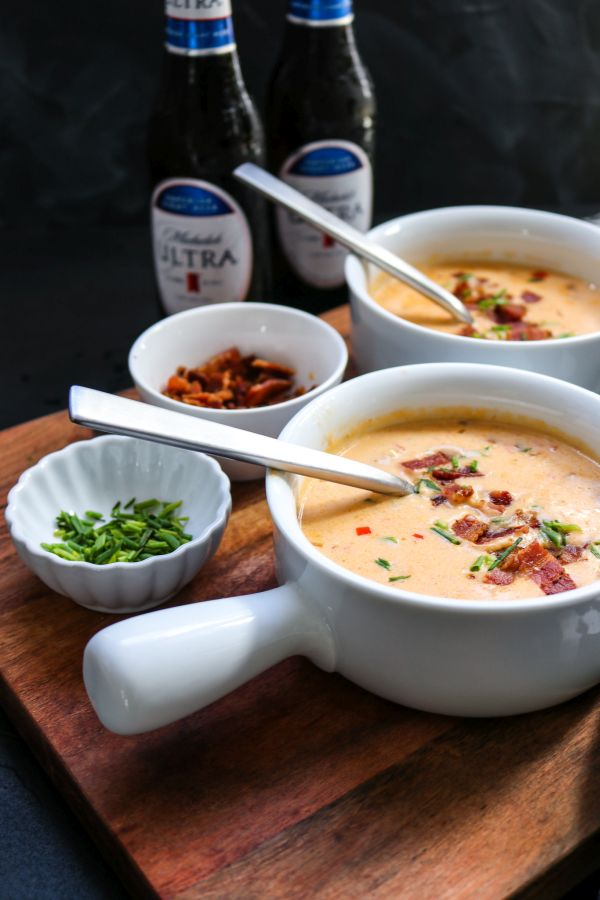 Michelob ultra low carb beer cheese soup in white bowls with spoons