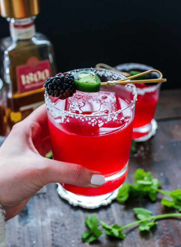 A person holding a glass with a jalapeno blackberry margarita in it.