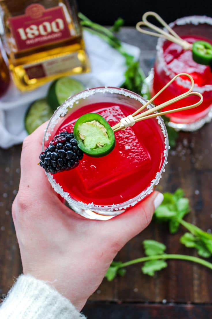 A hand holding a low carb blackberry jalapeno margarita