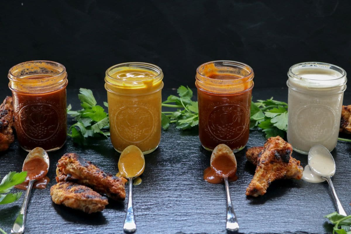 Jars of different keto BBQ sauces with spoons and chicken wings.
