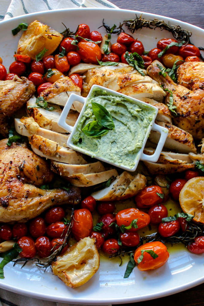 The Best Foolproof Easy Weeknight Roasted Chicken cut on a platter with basil aioli and tomatoes