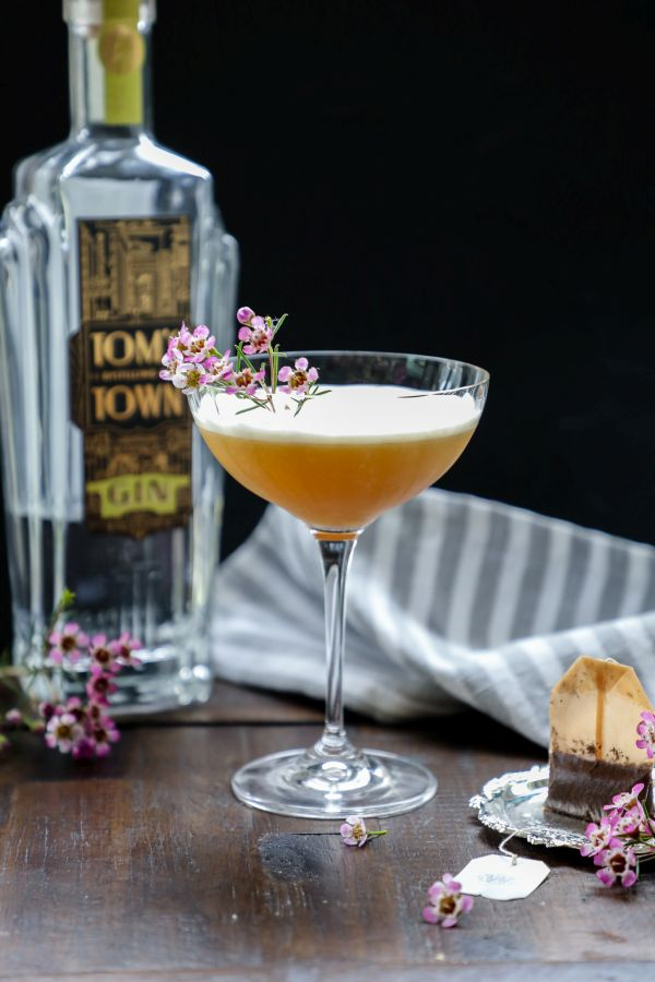 Keto earl grey gin fizz cocktail on a brown table.