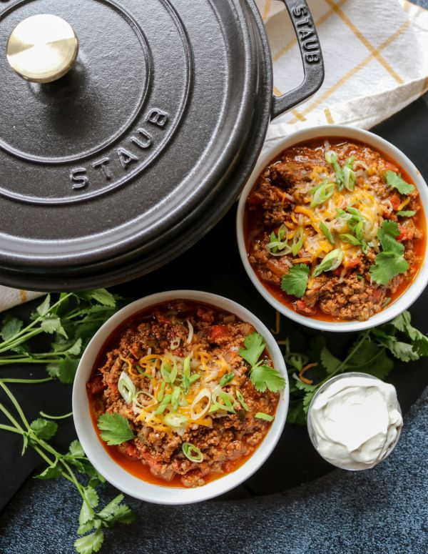 Two bowls of beef chili and a large black pot
