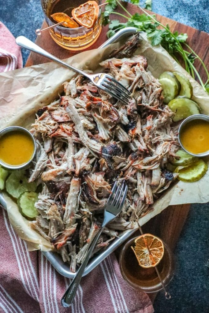 A platter of pulled pork, pickles, mustard, and forks on a table.