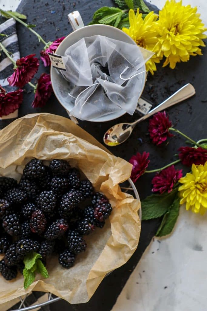 A close up of earl grey loose tea and fresh blackberries.