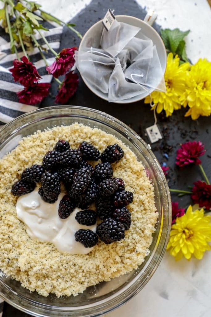 The bowl of dry ingredients with sour cream and fresh blackberries in it.