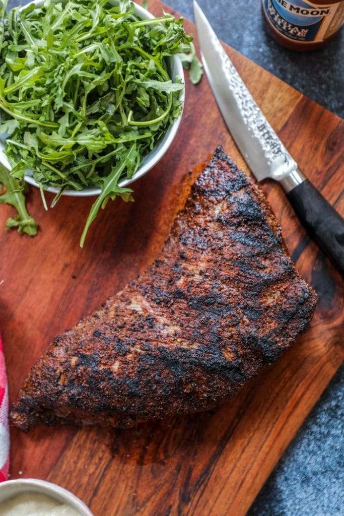 A whole tri tip on the cutting board with a knife.
