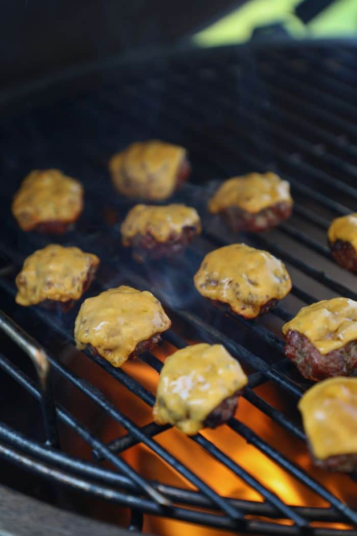 Mini burger patties on the grill with cheese