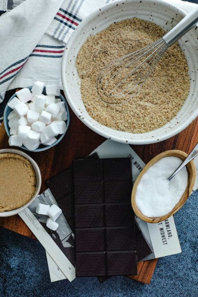 The ingredients placed on the table- toasted almond flour, keto marshmallows, and keto chocolate bars