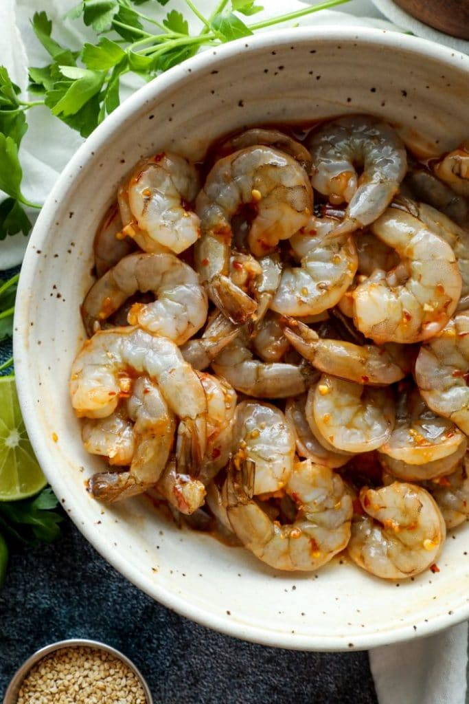 Shrimp coated in the chili sesame marinade in a white bowl.