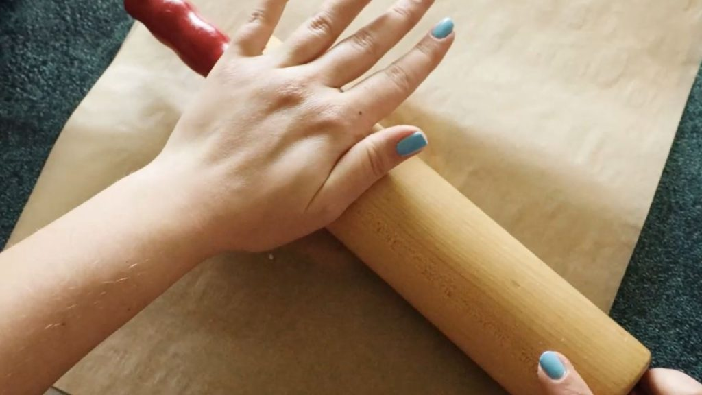 Parchment paper covered dough being rolled out with a rolling pin