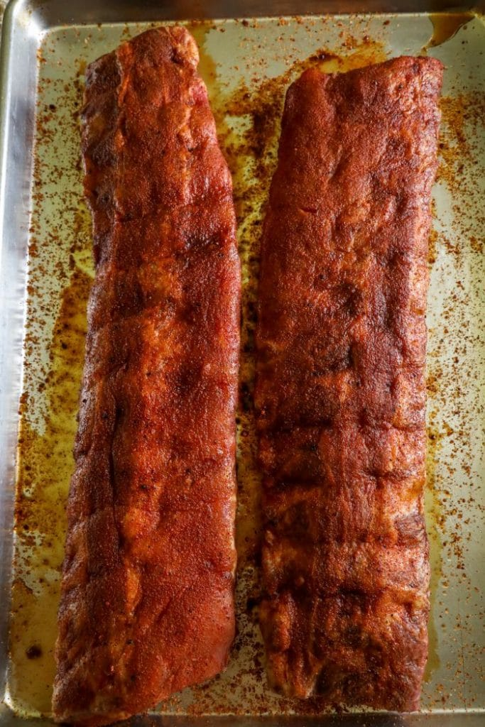 Raw ribs prepped with a dry rub and resting on a baking sheet