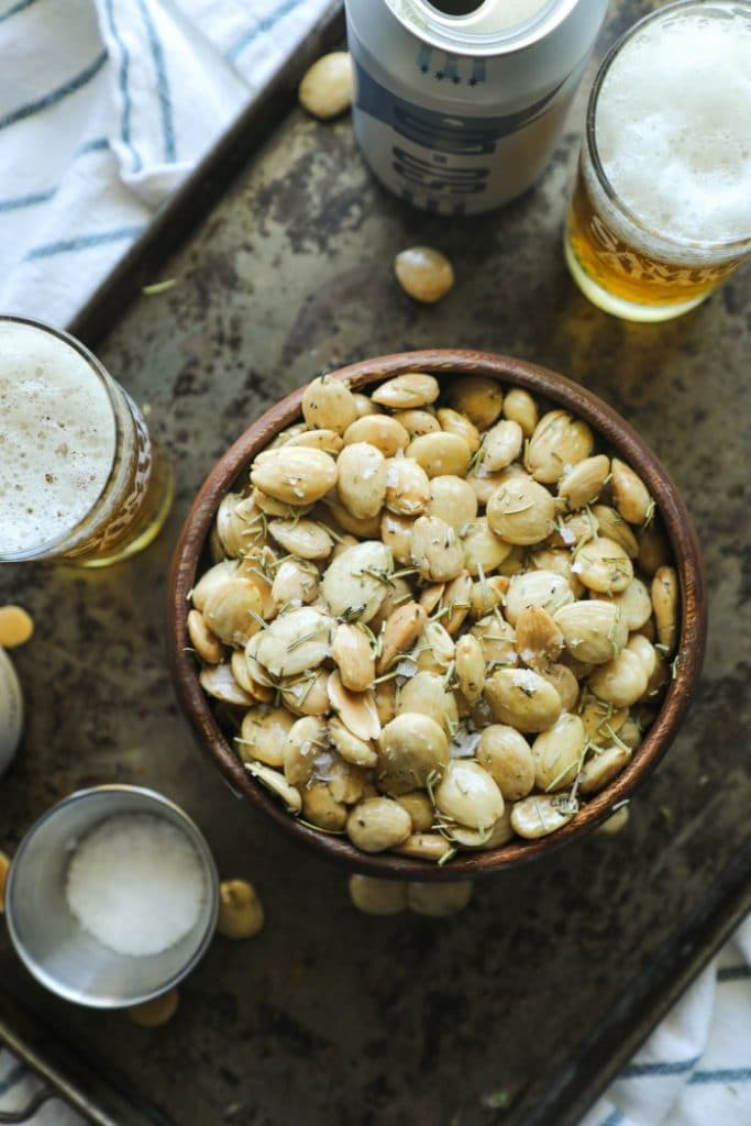 Herb Smoked Marcona Almonds with beer on a tray.