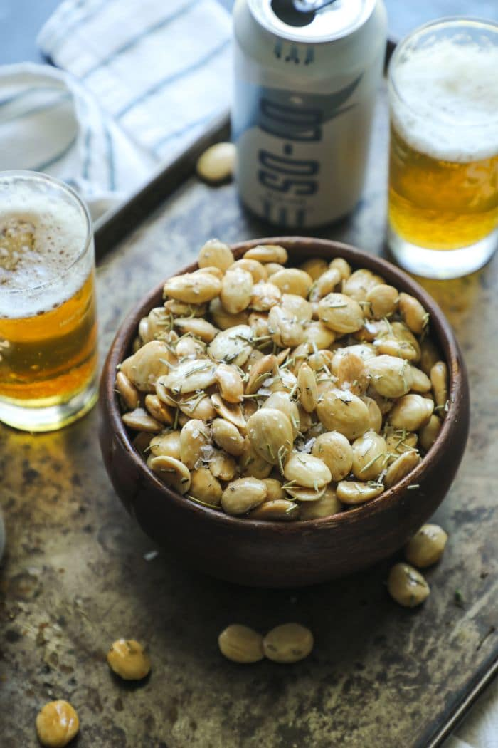 Smoked Marcona almonds in a bowl on tray with beer