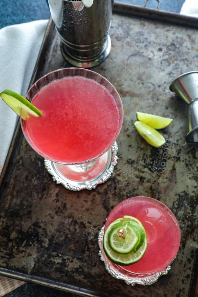 Top view of two cosmo cocktails on a metal tray.