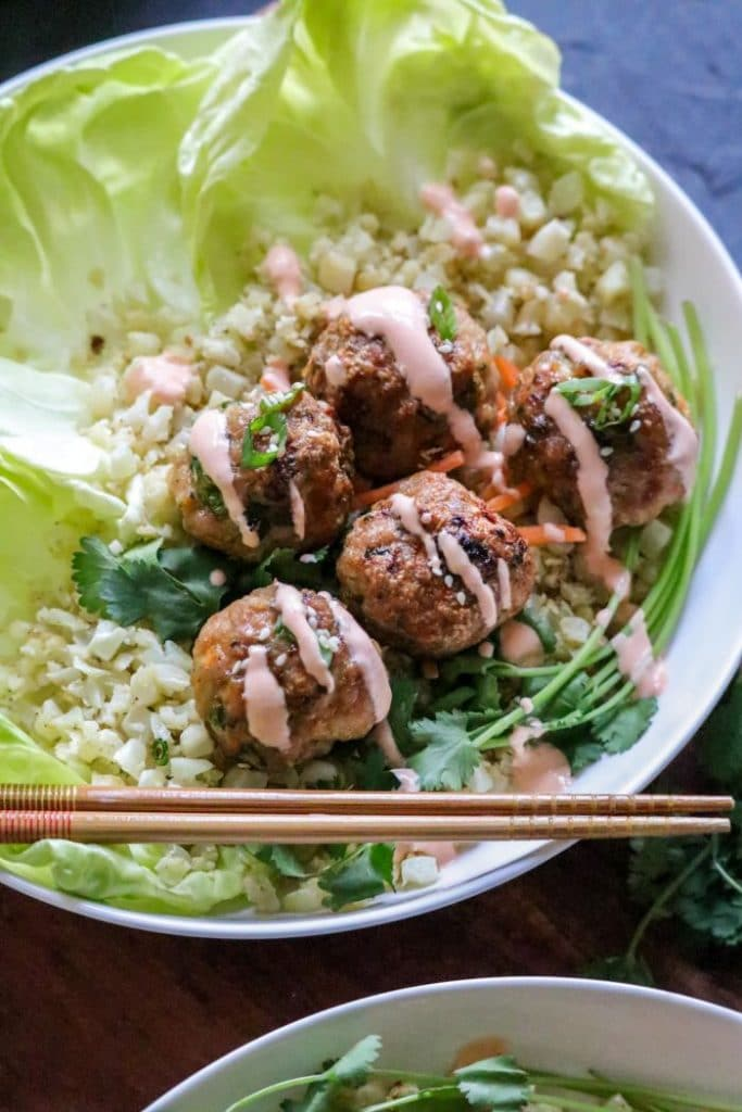 Lettuce cups and cauliflower rice in a bowl with egg roll meatballs and chopsticks.