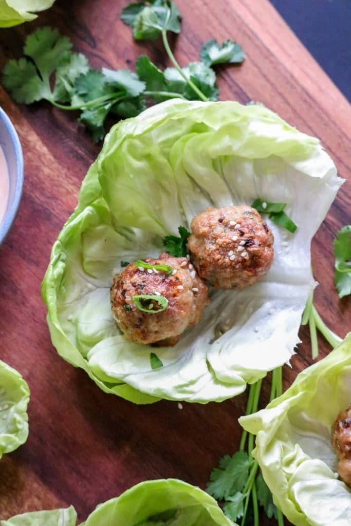 A lettuce cup sitting on top of a wooden table, with an egg roll meatball