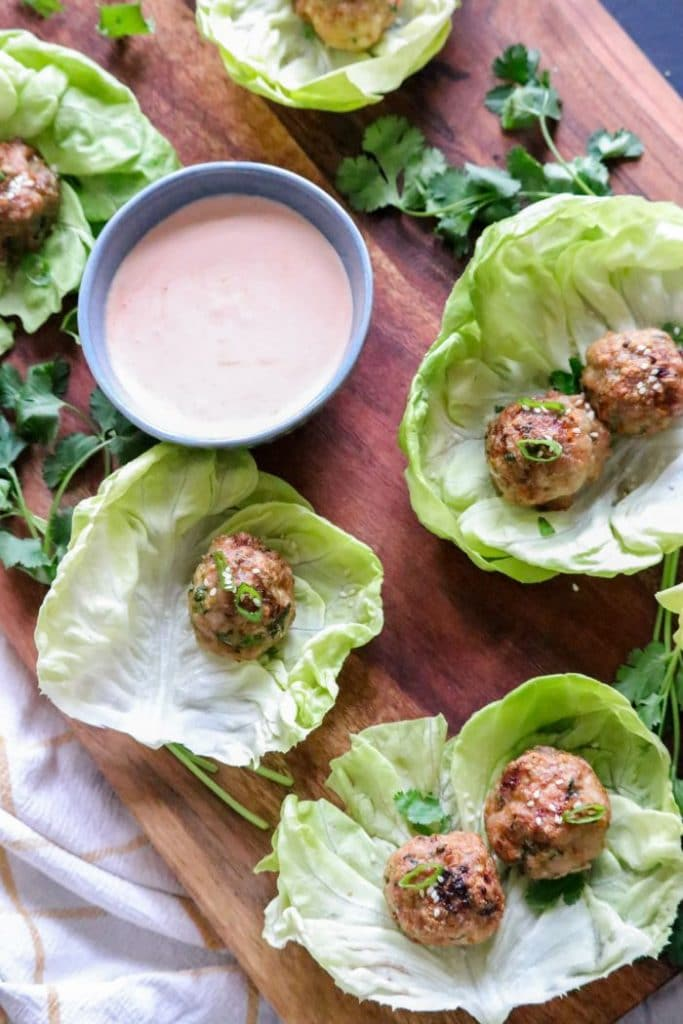 A bunch of food on a table, with Lettuce cups and meatballs placed inside.