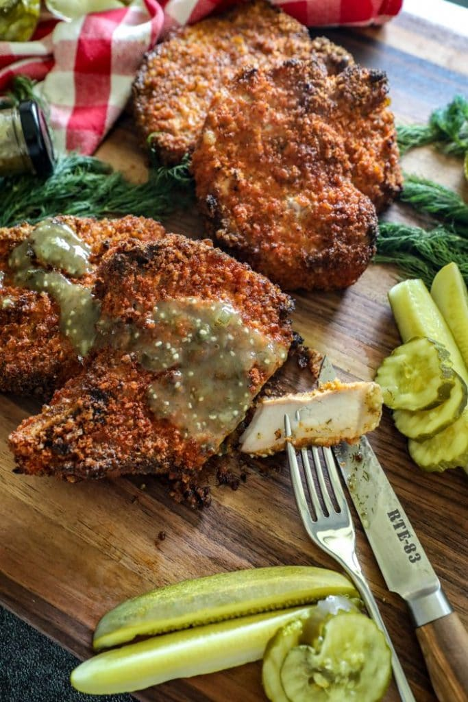 Smoked Dill Pickle Brined Pork Chops served with dill pickle hot sauce and cut into.