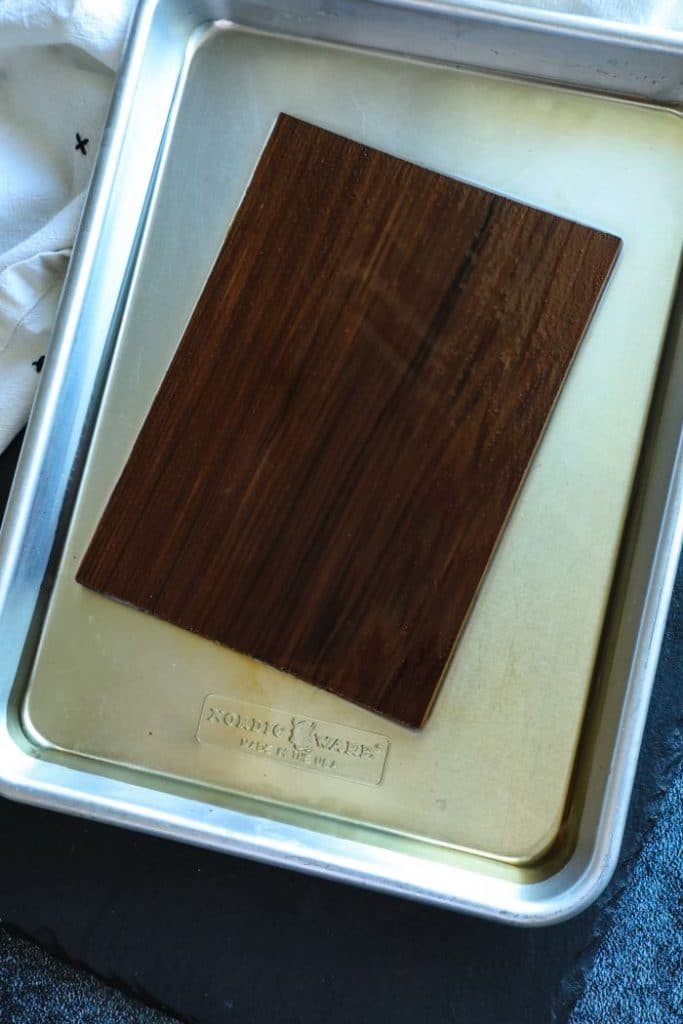 Cedar plank soaking in a pan of water.