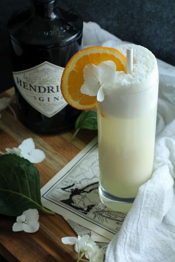Keto Creamsicle Gin Fizz on a board with a white towel and a bottle in the background.