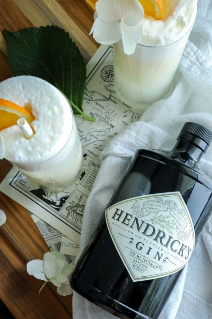 A bottle of Hendricks Gin on a white towel with two Two Keto Creamsicle Gin Fizz cocktails.
