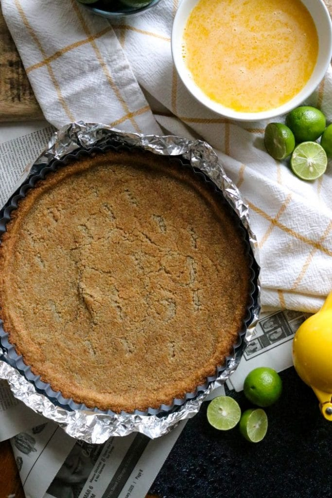 The partially baked keto key lime pie crust on a yellow towel and newspaper.