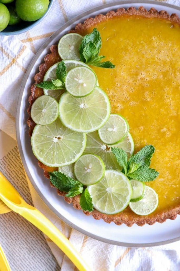 Close up of the keto key lime tart decorated with limes.