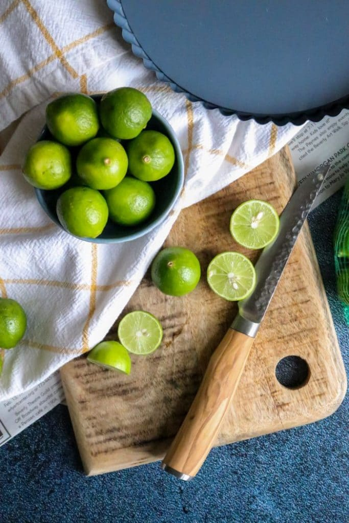 Key limes on a cutting board with a knife.