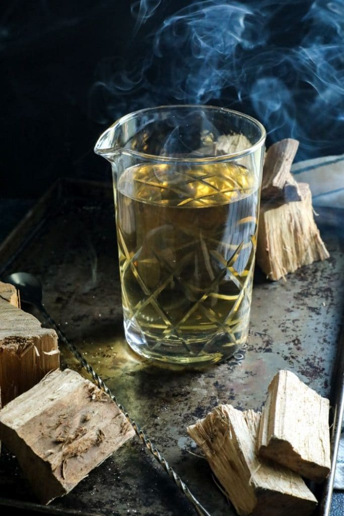 Smoke Infuse Simple Syrup with wood pieces, smoke, and a black tray.
