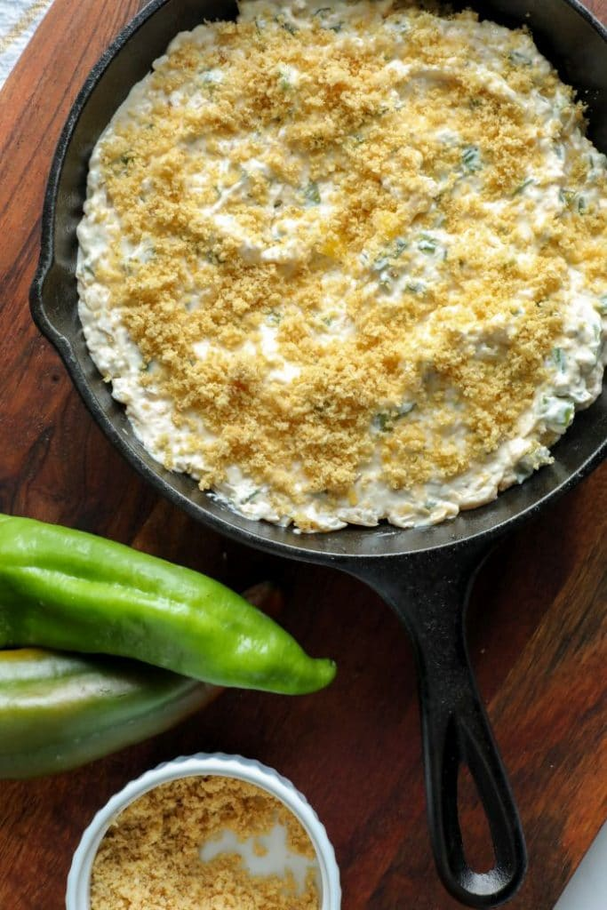 Smoked Hatch Chili Pepper Dip topped with pork rind crumbs in a cast iron pan.