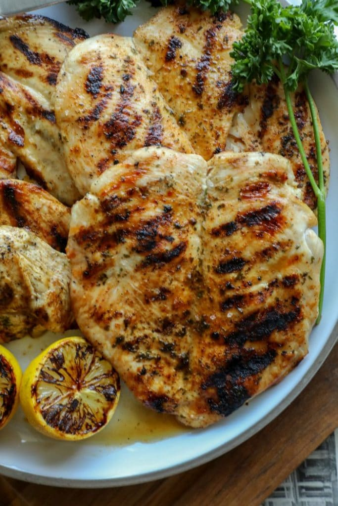A platter of perfectly grilled chicken breasts on a plate.