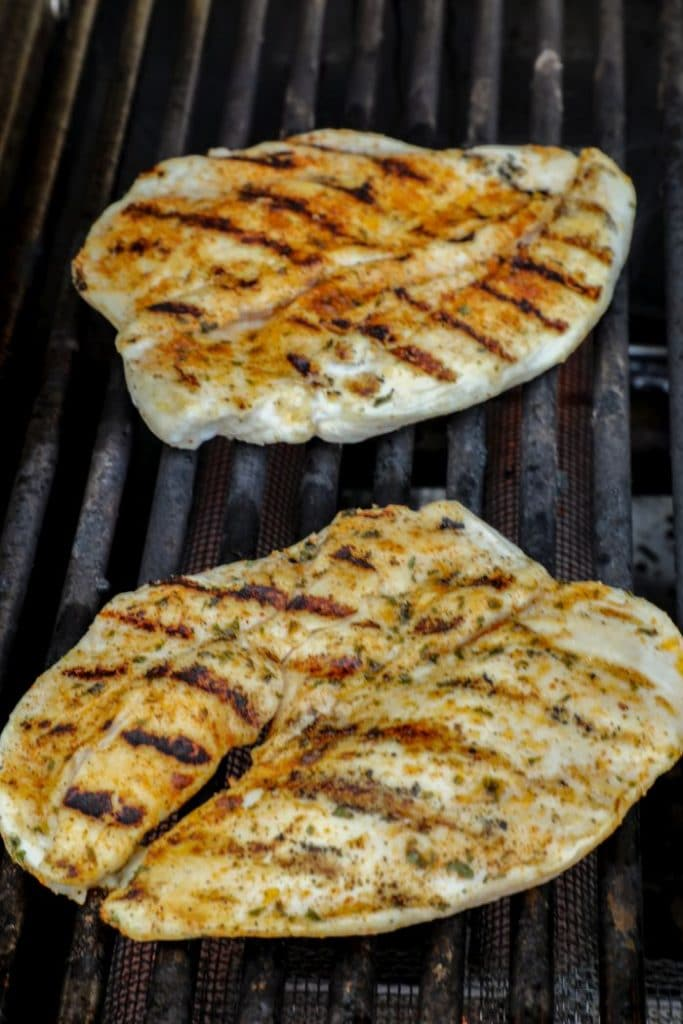 Butterflied chicken breasts over direct heat on a gas grill.
