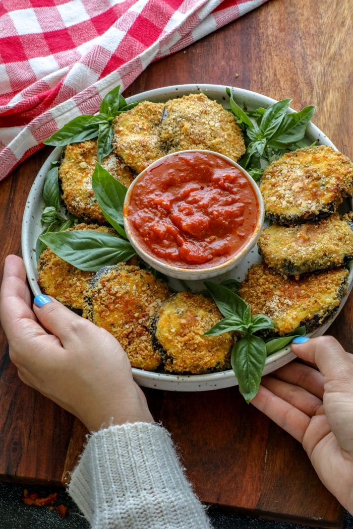 Two hands holding a plate with Crispy Keto Ricotta Stuffed Eggplant Rounds