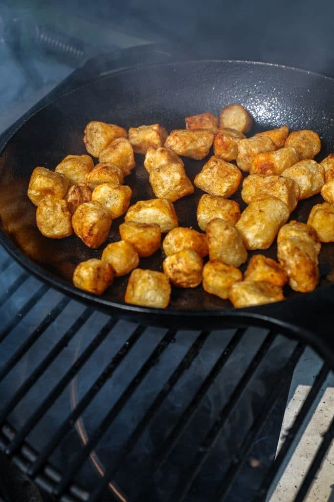 Cauliflower gnocchi being crisped on a cast iron on the big green egg grill.