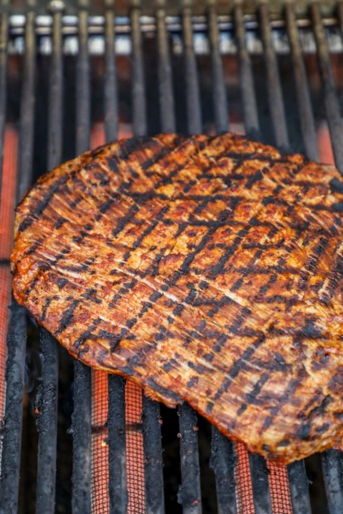 The adobo marinated flank steak being seared on the grill.
