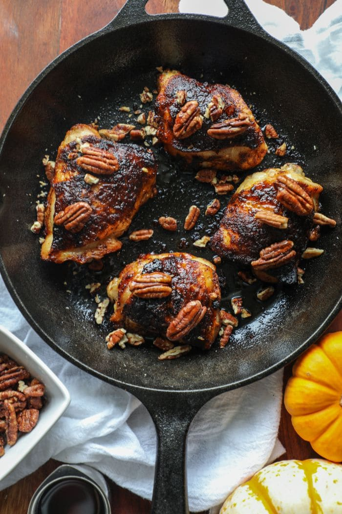 Grilled Crispy Maple Pecan BBQ Chicken Thighs in a skillet