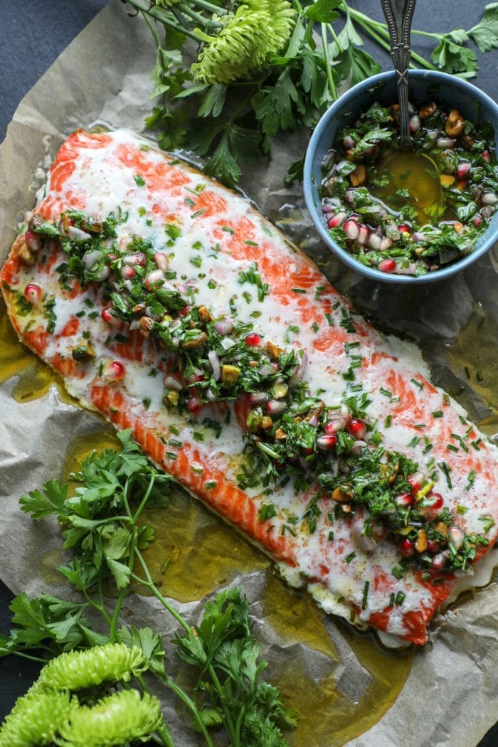 Butter Basted Slow Roasted Salmon with chimichurri over it on parchment paper