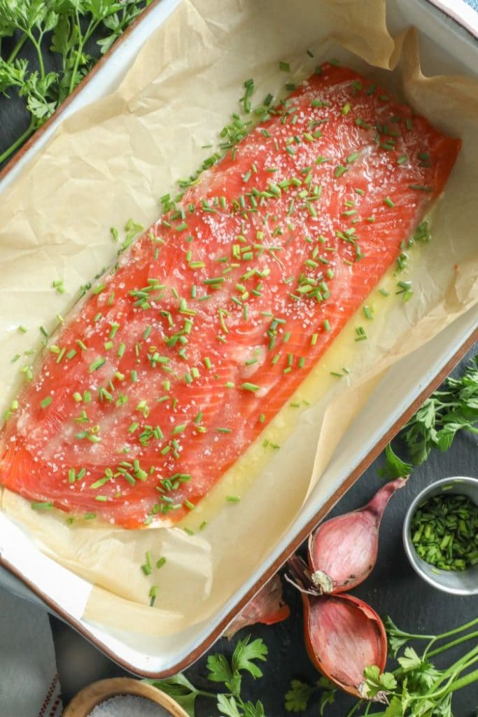 Slow roasted salmon with butter, salt, and chives over it in a baking dish.