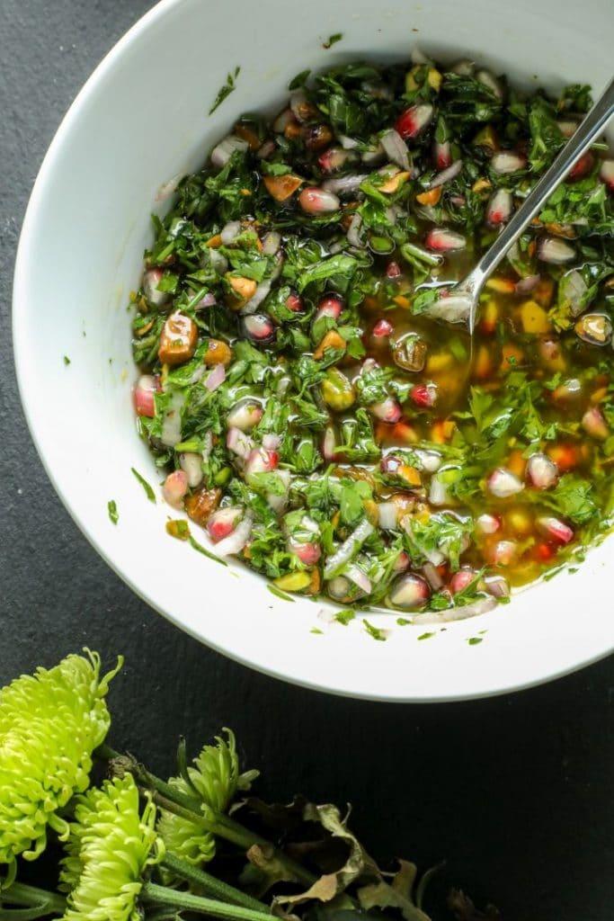 Pistachio and pomegranate chimichurri in a white bowl.