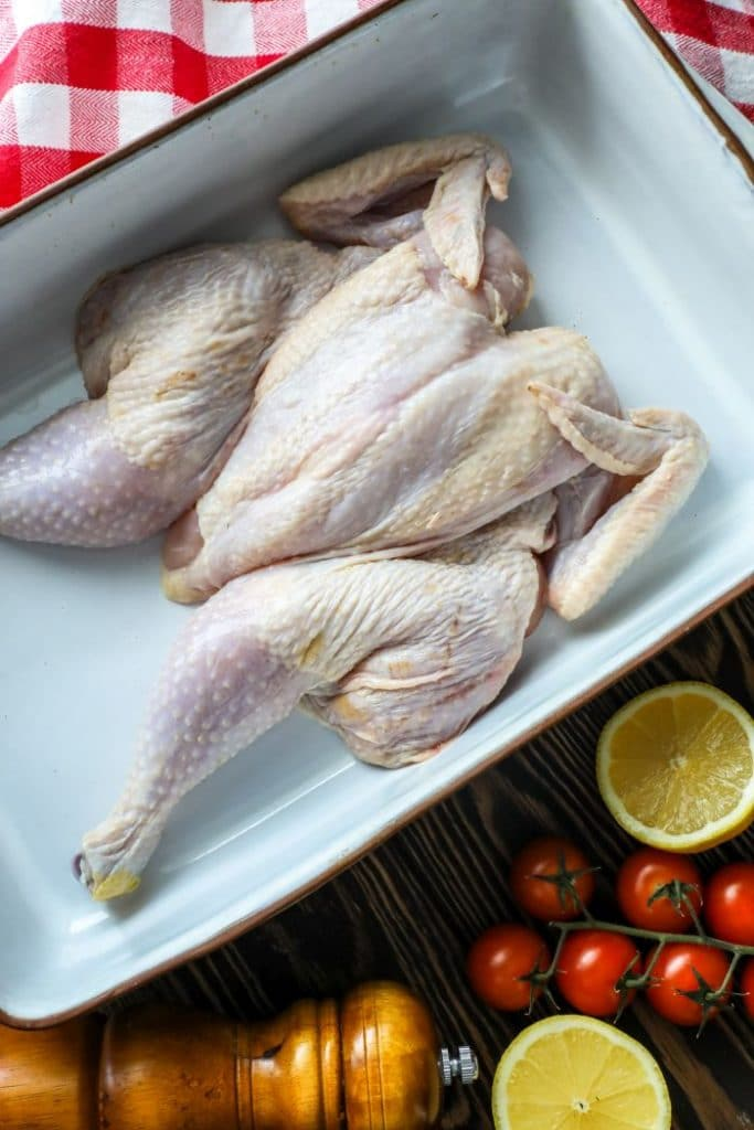 How To Roast Or Grill A Spatchcock Chicken - Raw chicken in a pan