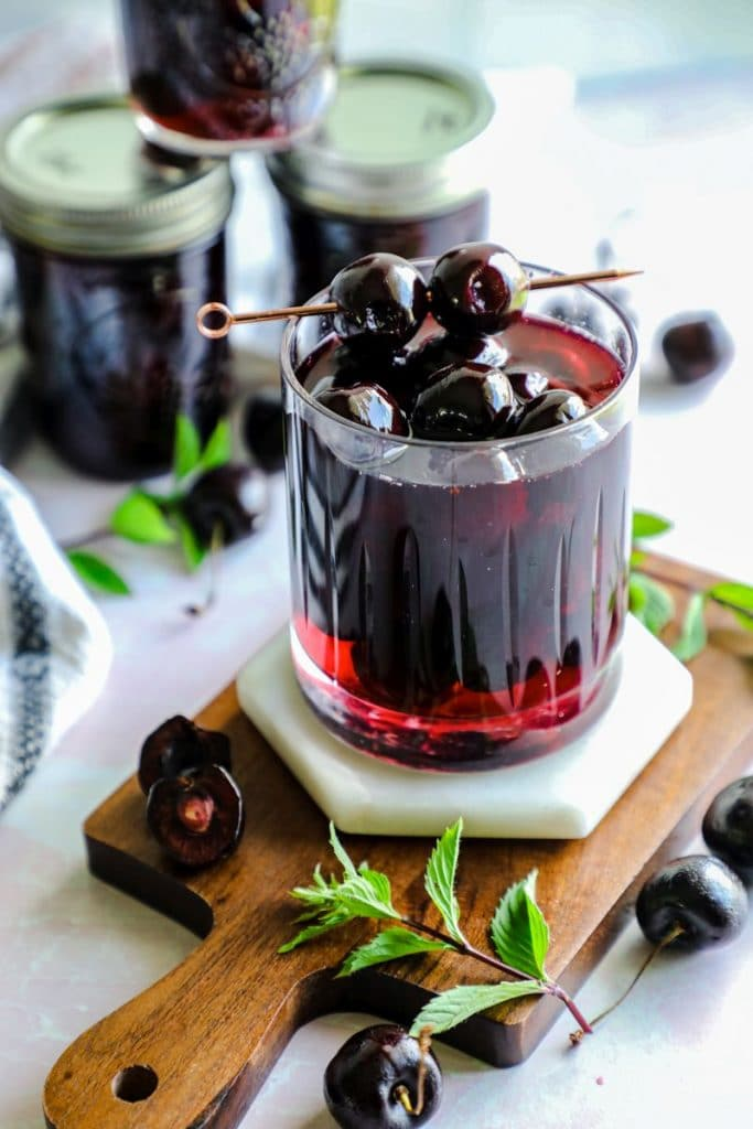 a glass filled with homemade maraschino cherries